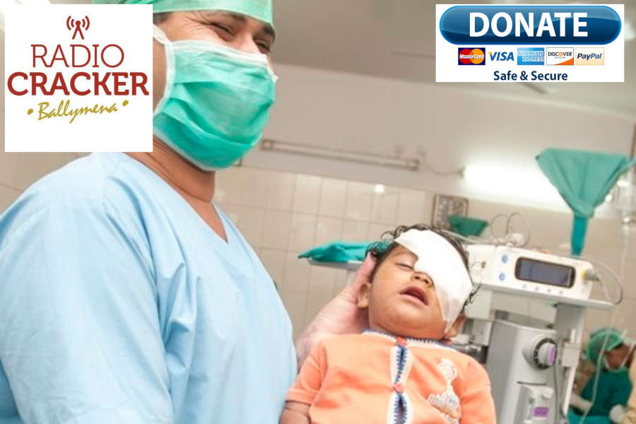 Indian medical assistant holding a child after a cataract operation